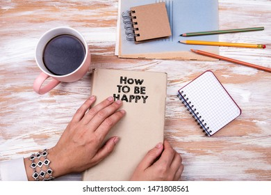 How to be happy. Hands holding book on office table