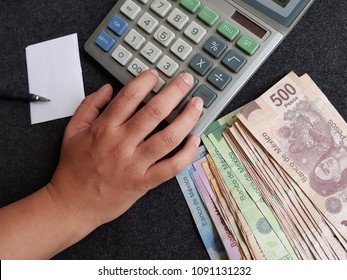 How to better manage money, hand pressing key of a calculator along with Mexican banknotes and note sheet