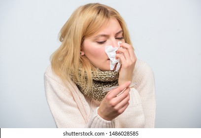 How to bring fever down. Fever symptoms and causes. Sick girl with fever. Girl sick hold thermometer and tissue. Measure temperature. Break fever remedies. Seasonal flu concept. Woman feels badly.