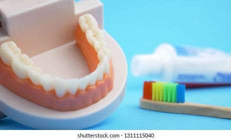 How to brushing teeth by rainbow bamboo toothbrush on back blue background with toothpaste. Concept dental hygiene