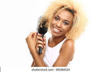 How to care for your hair? Dark skinned young woman combs her hair brush