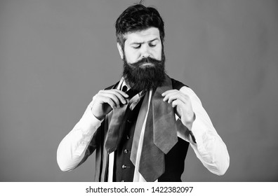 How to choose right tie. Classic style. How to match necktie with shirt and suit. Man bearded hipster hold few neckties on blue background. Guy with beard choosing necktie. Gentlemens guide.