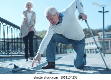 How could this happen to me. Selective focus on an elderly man leaning on one knee while trying to pick up his crutch after falling to the ground while promenading with his wife.