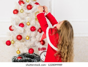 How to decorate christmas tree with kid. Let kid decorate christmas tree. Favorite part decorating. Getting child involved decorating. Girl long hair hold balls ornaments white interior background.