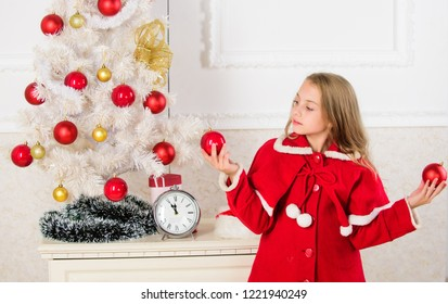 How to decorate christmas tree with kid. Let kid decorate christmas tree. Favorite part decorating. Getting child involved decorating. Girl smiling face hold balls ornaments white interior background.