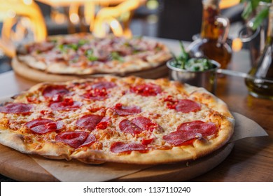 How delicious pepperoni pizza on wooden restaurant table.