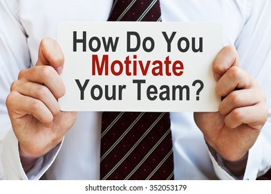 How Do You Motivate Your Team ? Businessman holding a card with a message text written on it