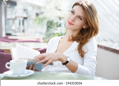 How to enjoy life / photo of beautiful woman sitting in a cafe with a book