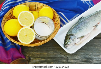 How to get rid of fishy smell in fish before cooking. Fish,lemon and salt in the basket on wooden background.