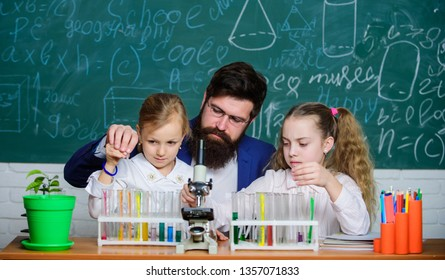 How to interest children study. Explaining biology to children. Fascinating biology lesson. School teacher of biology. Man bearded teacher work with microscope and test tubes in biology classroom.