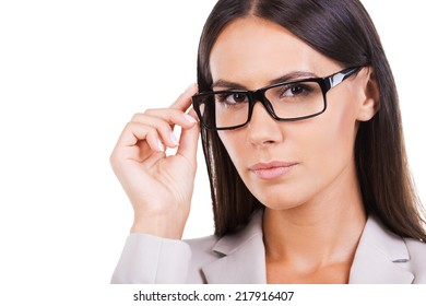 How may I help you? Beautiful young businesswoman in suit adjusting her eyeglasses and looking at camera while standing against white background