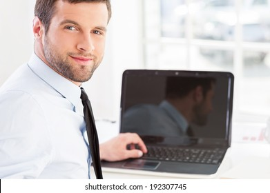 How may I help you? Handsome young man in formal wear working on laptop and looking over shoulder while sitting at his working place