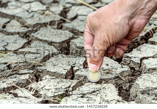 How much does climate change cost? Climate change leads to extreme weather events which cause considerable economic damage. A hand puts a two-euro coin in the dried up ground.