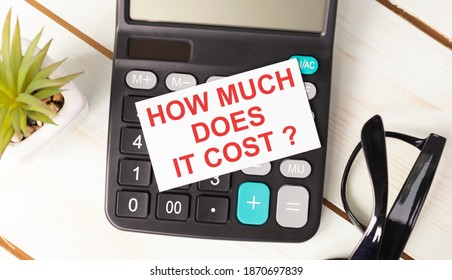 How Much Does it Cost write on sticky note isolated on wooden table.