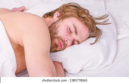 How much sleep you actually need. Man handsome guy lay in bed. Get adequate and consistent amount of sleep every night. Expert tips on sleeping better. Bearded man sleeping face relaxing on pillow.