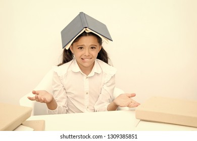 How is it possible to learn. Girl child confused exhausted with book roof on head white background. Schoolgirl tired of studying and reading. Kid school uniform tired face not want continue reading.