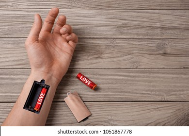 How to recharge the energy of love. Word LOVE is written on the battery. Hand of a man with a slot for charging batteries. Copy space for text