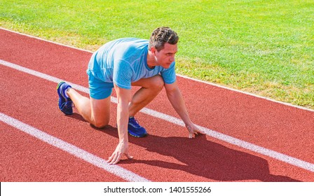 How to start running. Sport tips from professional runner. Man athlete runner stand low start position stadium path. Make effort for victory. Runner ready to go. Adult runner prepare race at stadium.