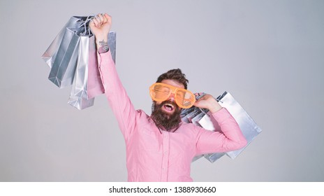 How to stop buying things you dont need. Obsessed with shopping. Addicted consumer concept. Man bearded hold shopping bags. Shopping dumb wasting money. Stupid things you do with your money.