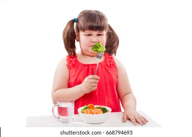 How to teach children to eat healthy food. Girl eats broccoli, sits with salad isolated on white background