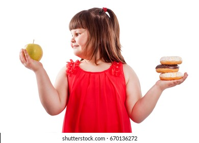How to teach children to eat healthy food. Girl chooses what to  eat donuts or fresh apple, isolated on white background - 4