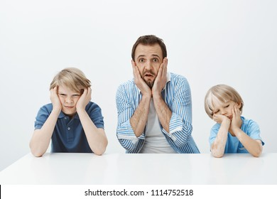 How they quickly grew up. Portrait of shocked anxious european father sitting with sons, holding hands on face and dropping jaw, feeling nervous while siblings are bored and careless over gray wall