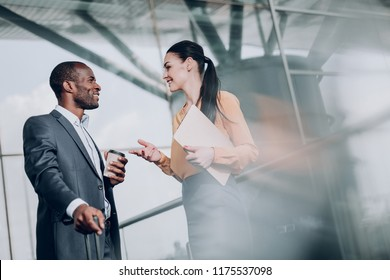 How are things. Waist up portrait of business lady holding folder and talking with her colleague, while drinking coffee. They are smiling looking at each other