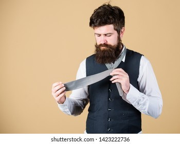 How to tie necktie. Start with your collar up and the tie around your neck. How to tie simple knot. Man bearded hipster try to make knot. Different ways of tying necktie knots. Art of manliness.