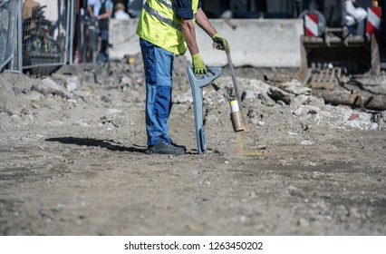 How to trace power cables with the cable finder. Electric technical worker carries out a work of tracking the new power line inside a construction site with a colored spray can.