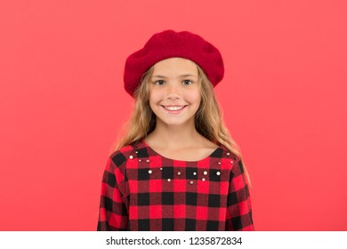How wear beret like fashion girl. Kid little girl with long hair posing in hat and checkered dress on red background. Fashionable beret hat for female. French style beret hat. Beret style inspiration.