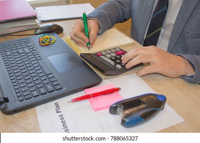 How to write business plan. Business proposal sample. Creating a business plan. Businessman working in his laptop in a modern office. Young Businessman Calculating Finance Bills