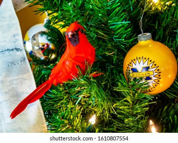 Howell, Michigan / USA - December 25 2019: Christmas tree ornaments with cardinal bird and Michigan bulb colors.