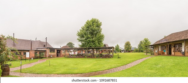 HOWICK, SOUTH AFRICA - MARCH 22, 2018: Panorama with businesses and outdoor eating area at Piggly Wiggly shopping centre, near Howick, in the Kwazulu-Natal Midlands Meander. Falling rain is  visible