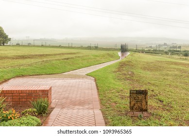HOWICK, SOUTH AFRICA - MARCH 23, 2018: The final plaque along the path with the statue of Nelson Mandela at his capture site in the back. At a specific viewpoint, the columns combine to form his face