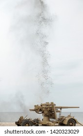 Howitzer on the sand with bomb explosion. Staging of a historic battle. World war, battle at the Baltic Sea. Poland.