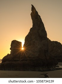 The howling dog or wizards hat in Bandon Beach on the Oregon Coast next to Face Rock. Silhouetted against the sunset with a sunstar through the rocks.