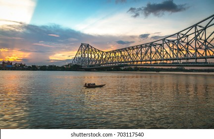Howrah bridge - A cantilever bridge on river Hooghly at sunset with moody sky.