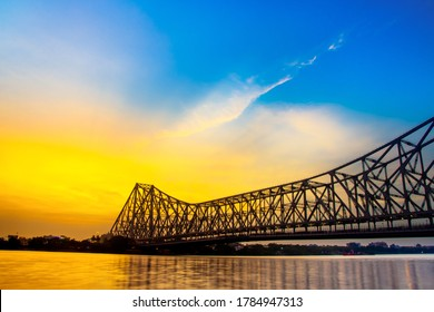 Howrah bridge - The historic cantilever bridge on the river Hooghly in West Bengal with twilight sky. Beautiful sunset view with blue sky and clouds.