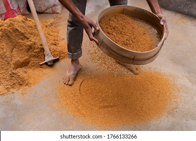 Howrah, West Bengal, India - 6th January 2020 : Indian labour separating sand and gravel manually using a sieve, for using the sand for cementing work, Image shot at daytime.