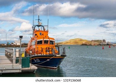 Howth, County Dublin, Ireland - February 20, 2019: Orange Irish Coast Guard Trent class lifeboat, docked at the RNLI Howth Lifeboat Station pier with lighthouse and the Ireland's Eye in the distance.