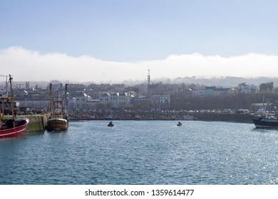 Howth, Dublin, Ireland, 28th March 2019. Howth Harbour with Howth Village in the background and fishing  trawlers tied up and clouds rolling over Howth Head,.