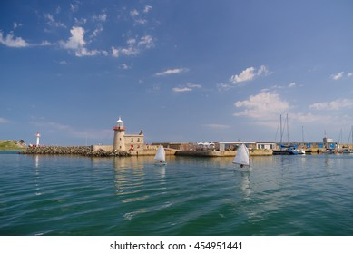 Howth Harbour and Lighthouse, Howth, Dublin, Ireland with some small sailing boats on a sunny day.