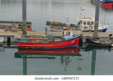 HOWTH, IRELAND, MARCH 30, 2019, Small fishing boats reflecting in the water in the harbour of the village of Howth,  30 March 2019
