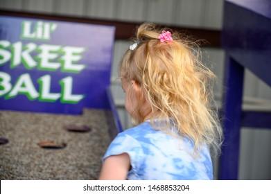 Hoxie, Kansas, USA - 7/2019: Caucasian girl playing Skee Ball at county fair