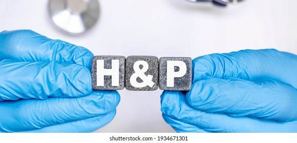 HP History and physical examination - word from stone blocks with letters holding by a doctor's hands in medical protective gloves