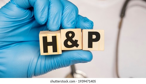 HP History and physical examination - word from wooden blocks with letters holding by a doctor's hands in medical protective gloves. Medical concept.