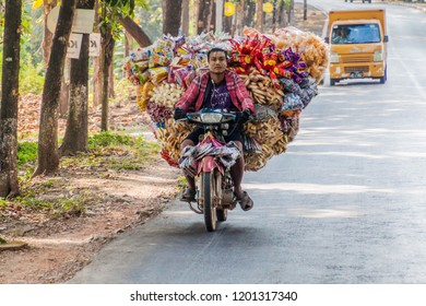 HPA AN, MYANMAR - DECEMBER 13, 2016: Local man on a heavily loaded motorbike near Hpa An.