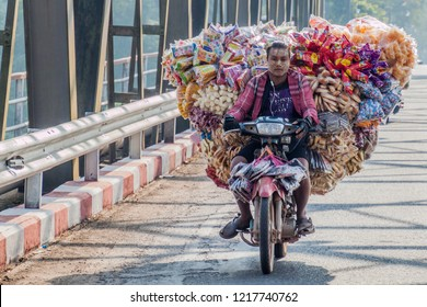 HPA AN, MYANMAR - DECEMBER 13, 2016: Local man on a heavily loaded motorbike crosses a bridge over Thanlwin (Thanlyin) river near Hpa An.