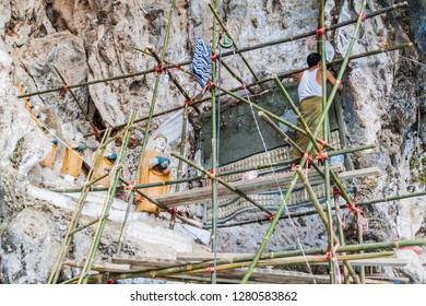 HPA AN, MYANMAR - DECEMBER 13, 2016: Worker on a scaffolding renovating a sculpture near Kaw Ka Taung cave near Hpa An, Myanmar