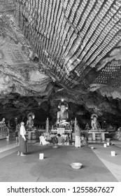 HPA-AN, MYANMAR - 19 NOVEMBER, 2018: Black and white picture of local people praying in front of Buddha Statues inside of Kaw Ka Thaung Cave, located close to Hpa-An, Myanmar